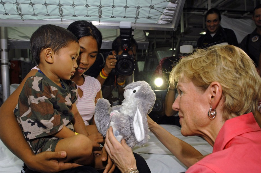 US Navy 070628-N-4954I-021 U.S. Ambassador to the Philippines, The Honorable Kristie A. Kenney, presents a stuffed bunny to a Filipino child as his mother holds him