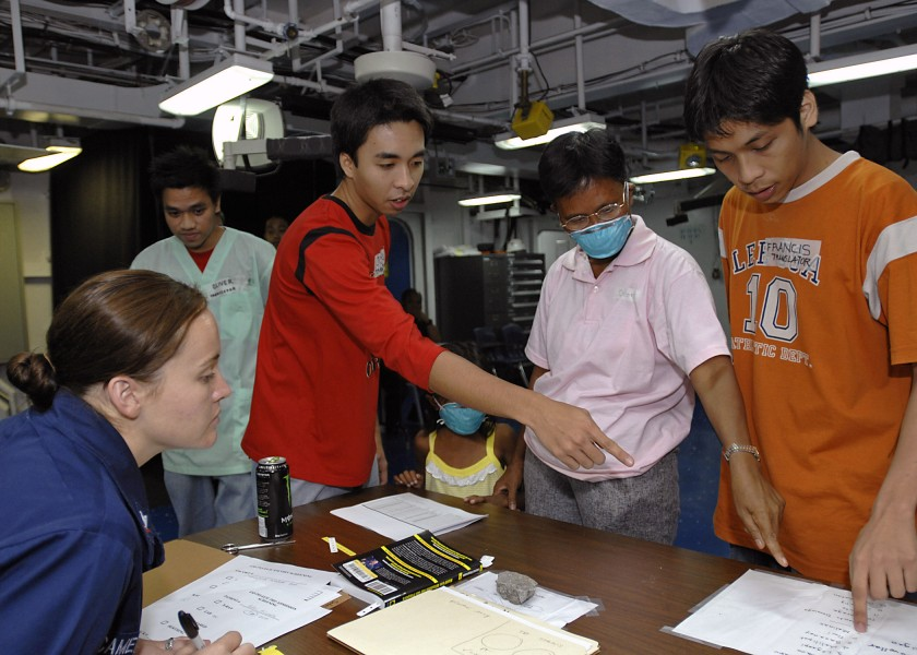 US Navy 070630-N-4954I-020 Aviation Ordnanceman 3rd Class Ashley Cameron and to two Filipino translators assist a Filipino patient during check in for medical care aboard amphibious assault ship USS Peleliu (LHA 5)