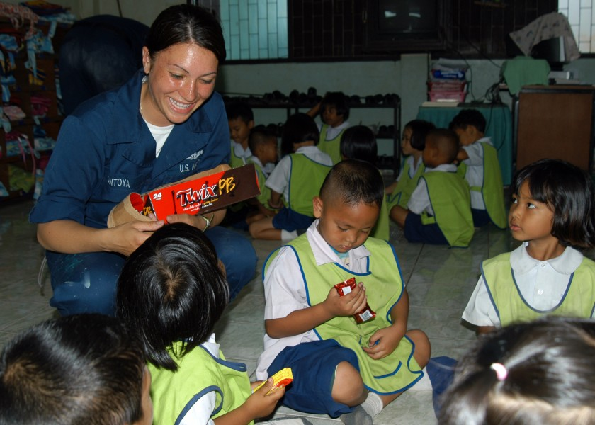 US Navy 090220-N-6692A-063 Aviation Ordnanceman Airman Francheska Montoya shares candy with a group of Thai kindergarteners