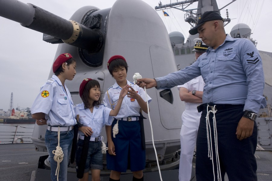US Navy 100105-N-3333H-001 Boatswain's Mate 2nd Class Anthony Ryan Mendez demonstrates knot-tying techniques to Japanese sea cadets during a tour aboard the guided-missile destroyer USS Curtis Wilbur (DDG 54)