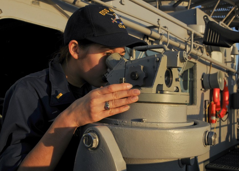 US Navy 110220-N-9793B-005 Ensign Leah M. Fontenot looks through a telescopic alidade on the ship's port bridge wing aboard the guided-missile crui