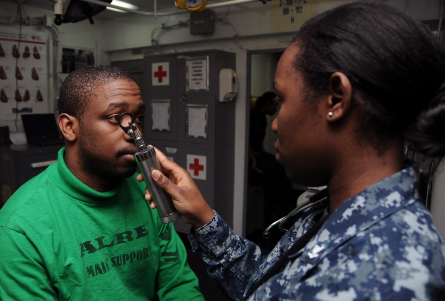 US Navy 120119-N-NB694-023 Hospital Corpsman 3rd Class Kerchelle Cortes conducts a medical examination on Aviation Boatswain's Mate (Equipment) 2nd