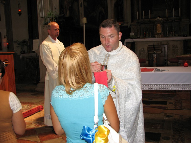 A young woman taking Jesus in the Holy Communion in Venice, Italy, European Union, August 2011, picture 16