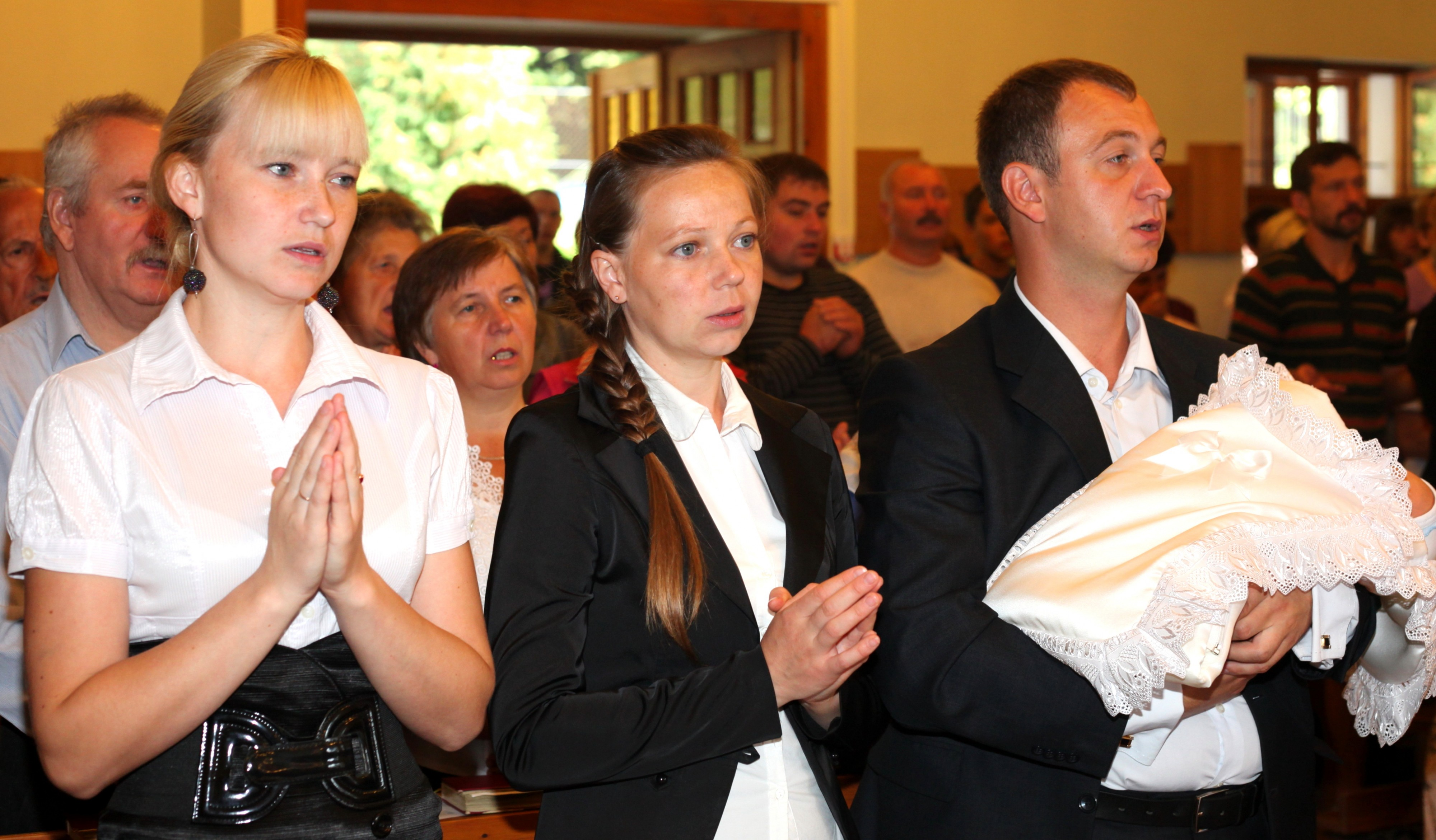 godmother and parents praying during the baptism of the baby-boy in the Catholic Church, photo 8
