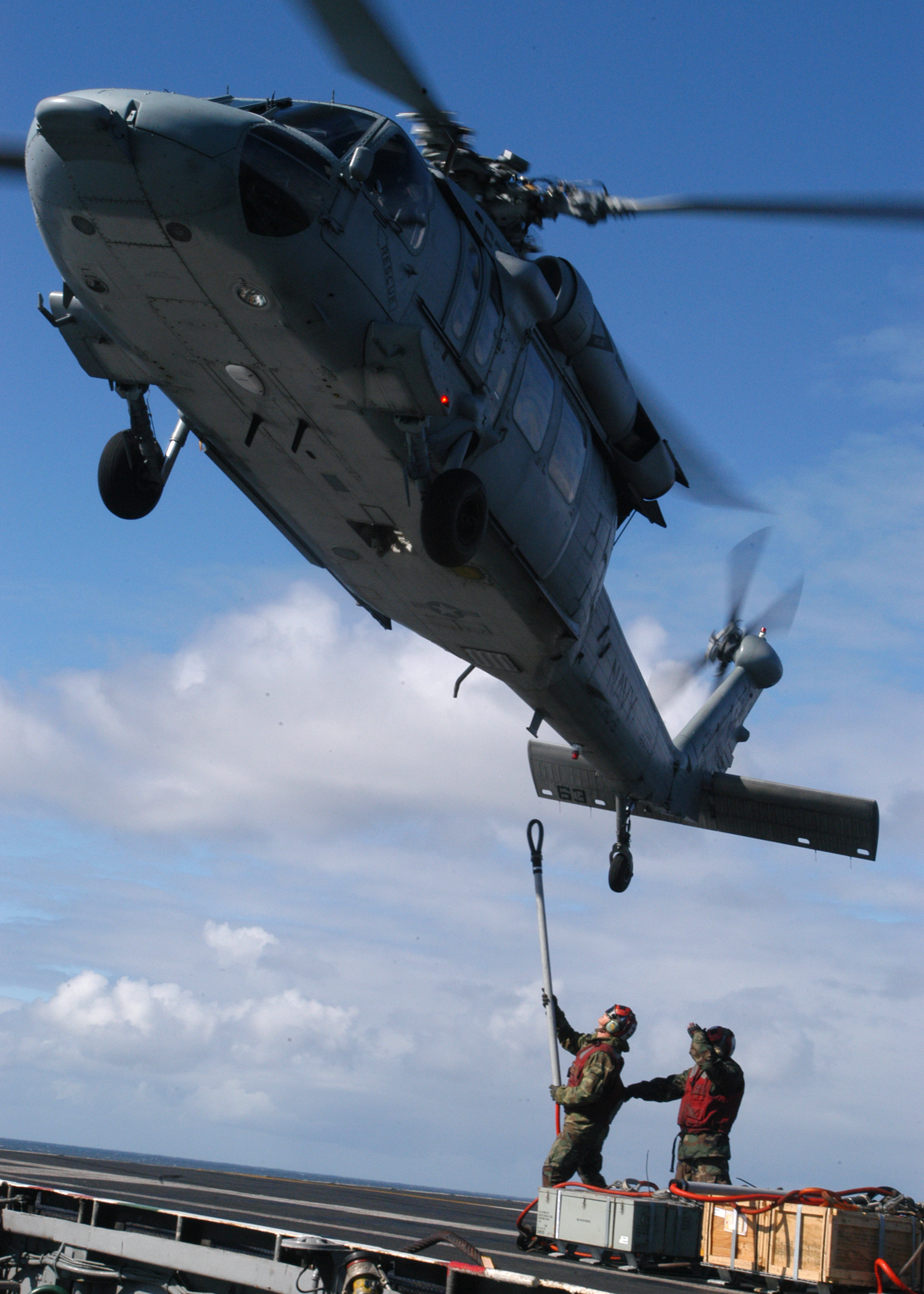 US Navy 040618-N-9742R-055 Aviation Ordnancemen uses a cargo pendant to attach a load of ordnance to a MH-60S Knighthawk