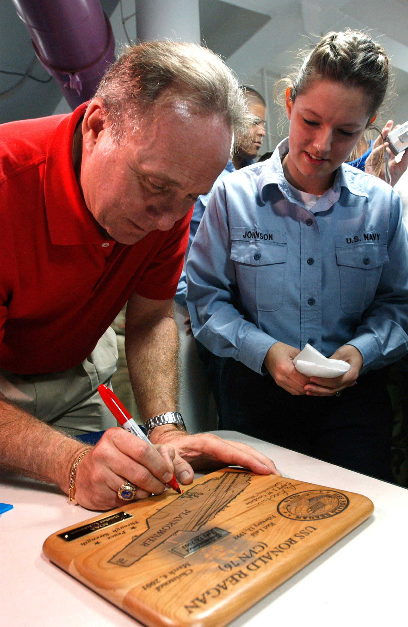 US Navy 040722-N-8148A-162 Michael Reagan, son of former President Ronald W. Reagan, autographs a plank owner plaque for Aviation Ordnanceman Airman Heather Johnson, of Saginaw, Mich