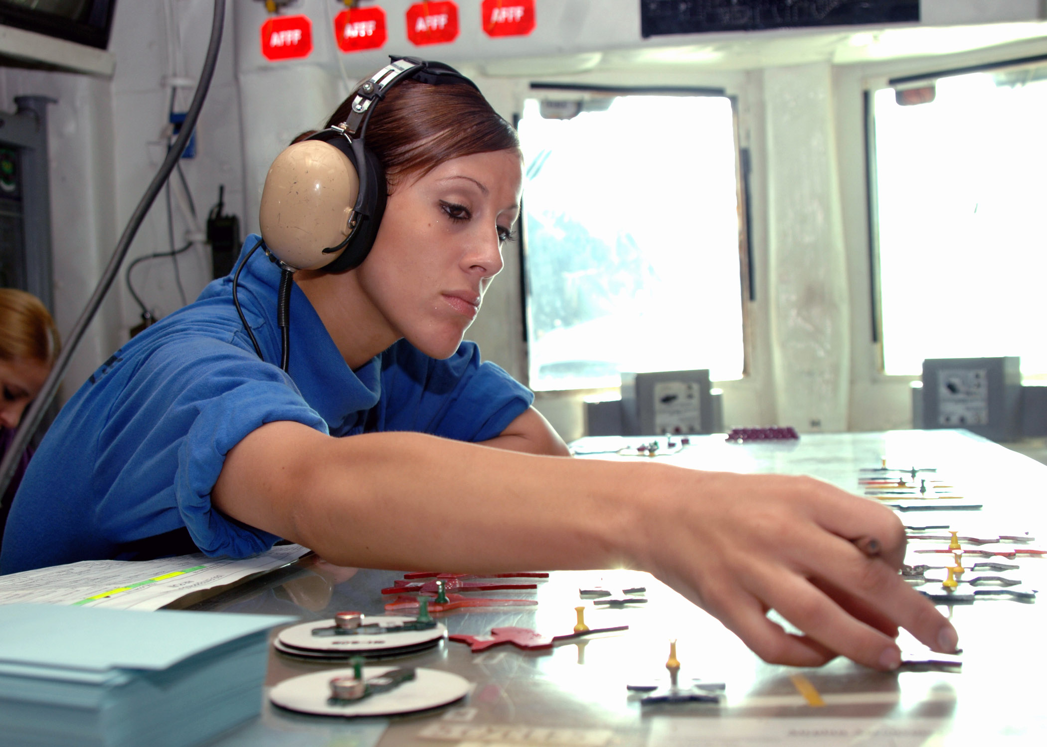 US Navy 071027-N-1287L-063 Aviation Boatswain's Mate (Handling) Airman Sarah McMillen places jet models in their respective positions on a scaled version of the flight deck aboard nuclear-powered aircraft carrier USS Enterprise