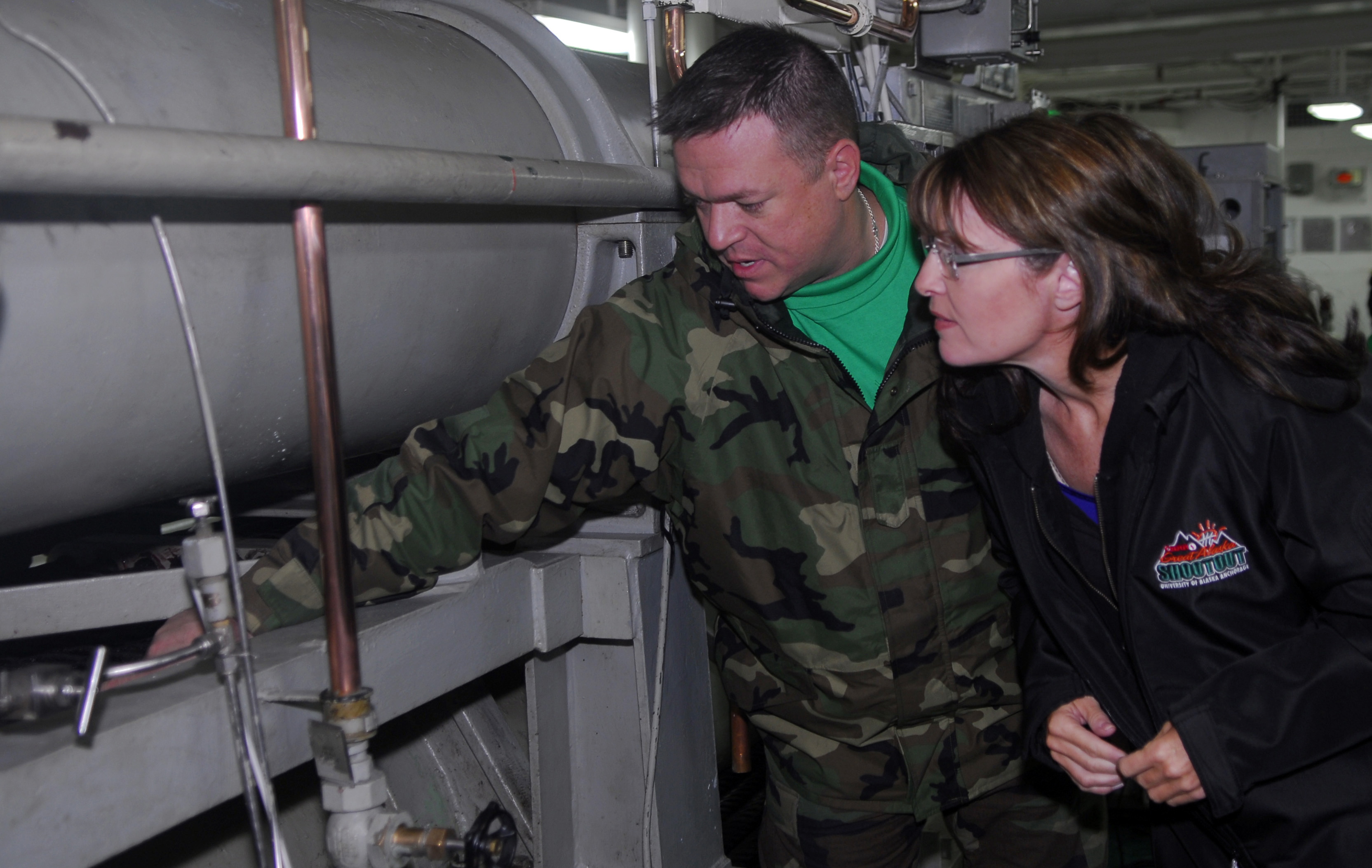US Navy 090622-N-2475A-050 Alaska Gov. Sarah Palin, right, listens as Aviation Boatswain's Mate (Equipment) 1st Class John Childs, from Fayetteville, N.C., explains the basic components and functions of an arresting gear engine