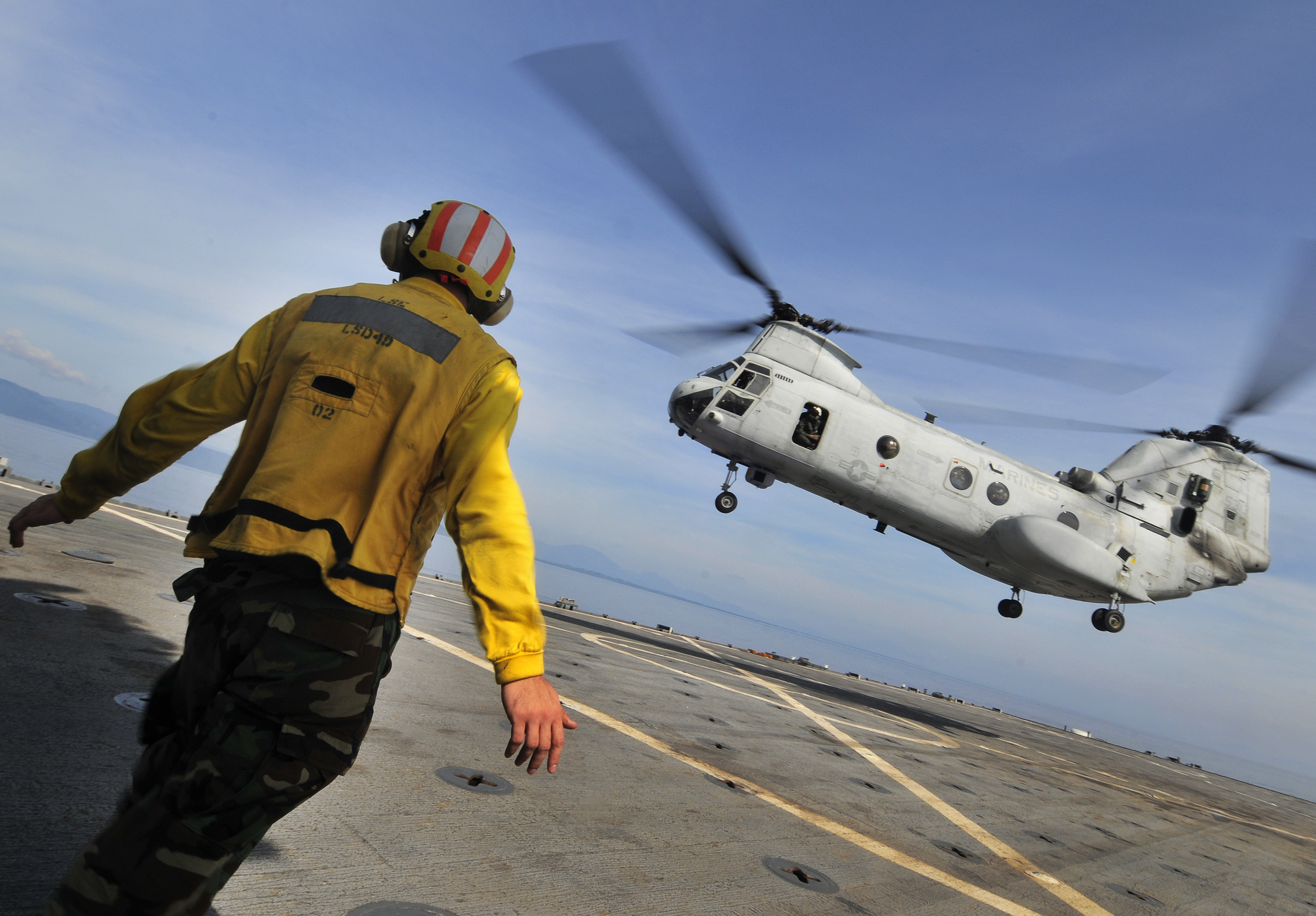US Navy 091020-N-0807W-406 Aviation Boatswain's Mate (Handling) Airman Zachary D. Bruton signals to a Marine Corps CH-46 Sea Knight helicopter aboard the amphibious dock landing ship USS Harpers Ferry (LSD 49)