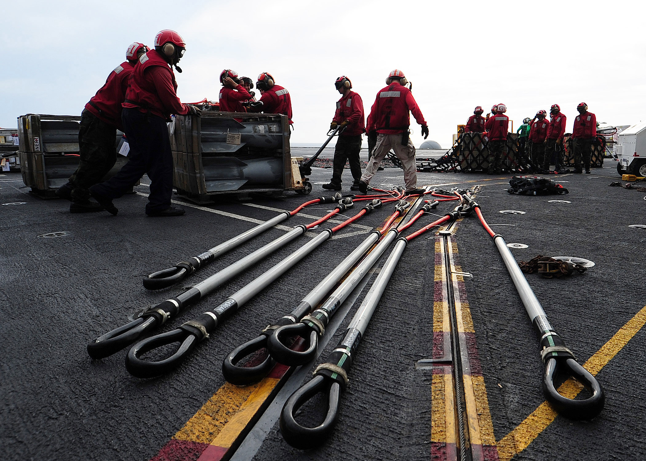 US Navy 100623-N-6720T-001 Aviation ordnanceman arrange munitions pallets before lowering them to the hanger bay of the aircraft carrier USS George Washington (CVN 73)