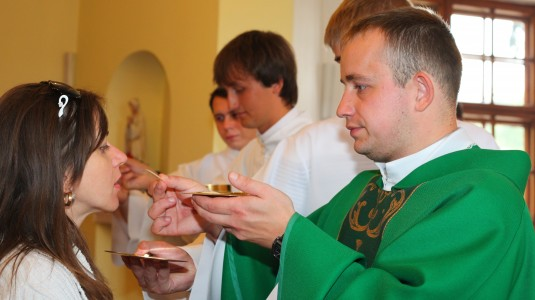a young Catholic woman takes Jesus Christ in the Holy Communion