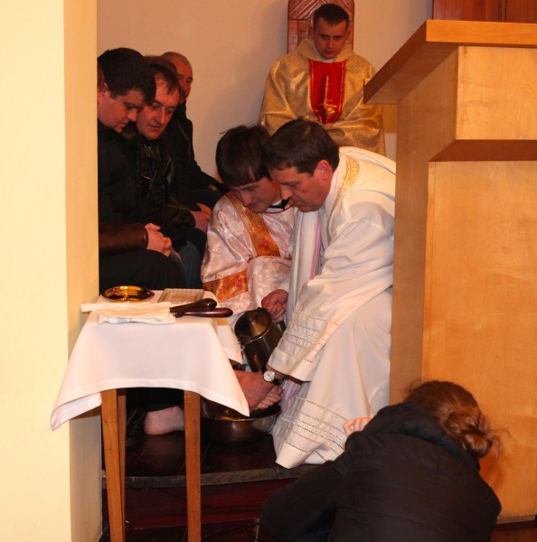 a Catholic priest washing feet of his parishiners