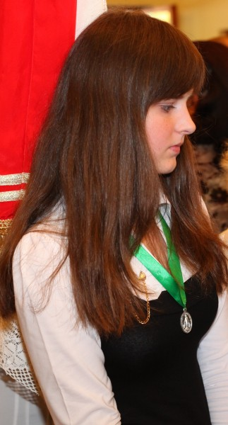 a young brunette Catholic girl at a Holy Mass
