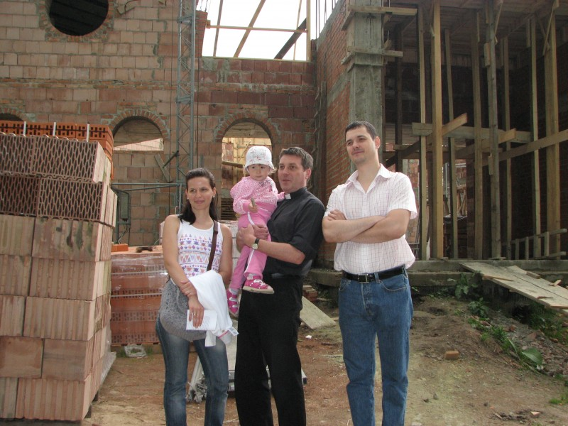 A Catholic priest (in the middle) with a young family near a Church which is being built, pic 2