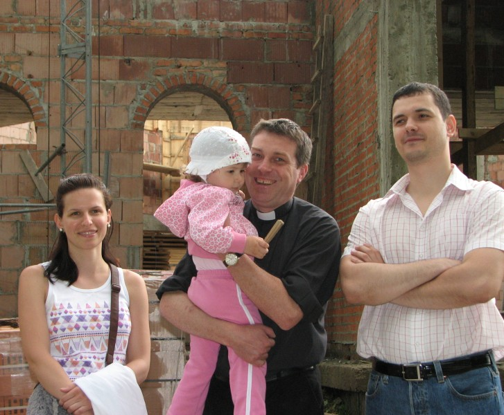A Catholic priest (in the middle) with a young family, pic 3