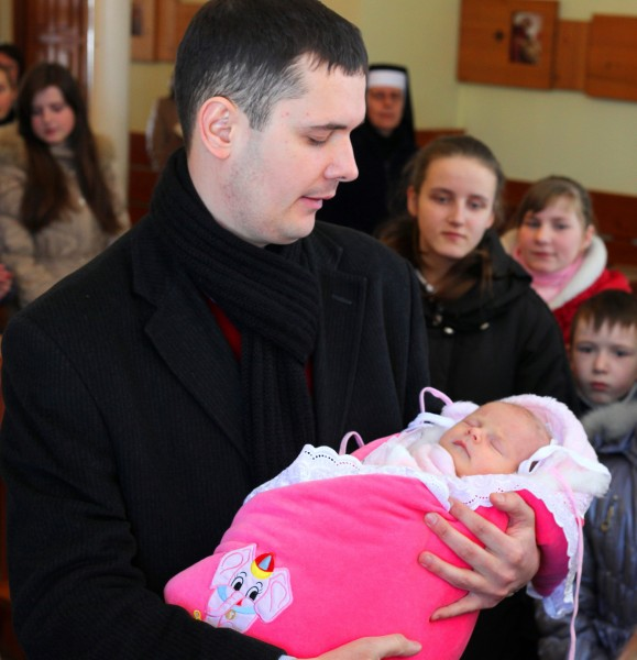 a father holding his baby daughter during her christening in a Catholic Church, photo 2
