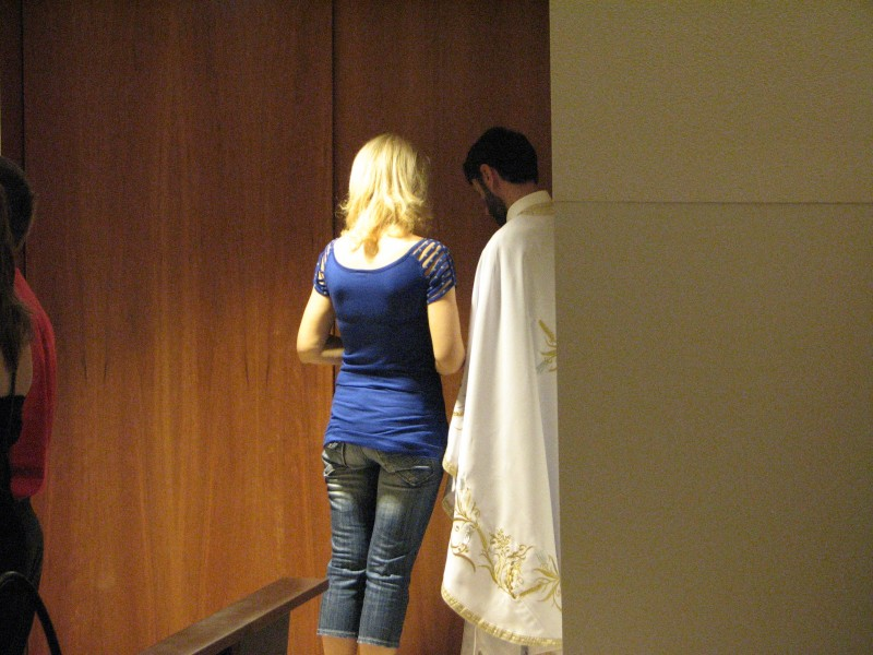 a girl confessing her sins to a Greek-Catholic priest in Fatima, Portugal