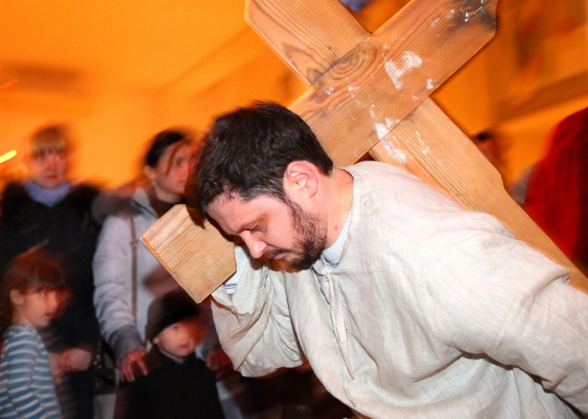 a man performing Jesus carring the cross