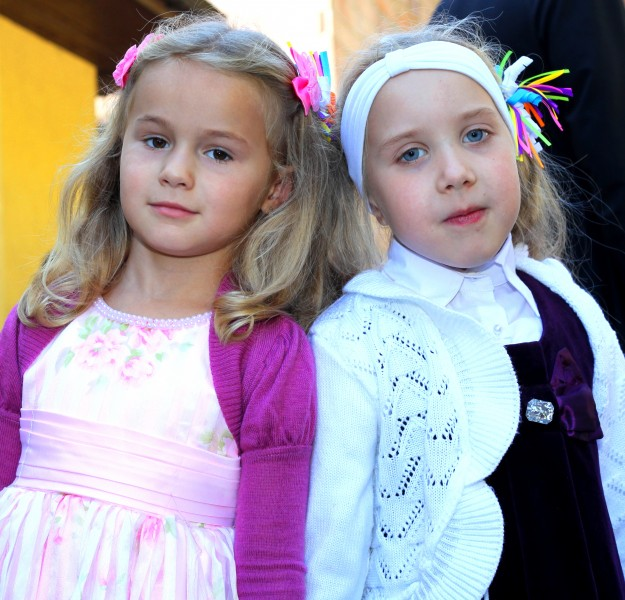 two Catholic child girls near a Church after the Holy Mass