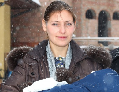 a beautiful Catholic godmother after the baptism of the baby, snowing, photo 12