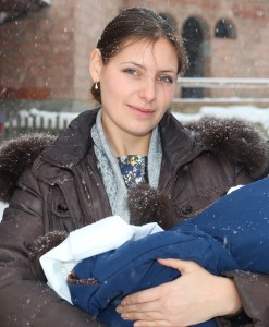 a beautiful Catholic godmother after the baptism of the baby, snowing, photo 5