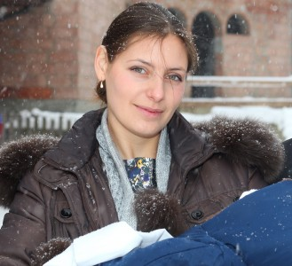 a beautiful Catholic godmother after the baptism of the baby, snowing, photo 6