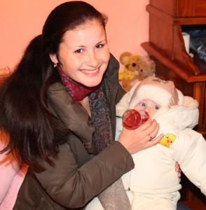 a beautiful smiling charming young brunette woman in a Church feeding a baby, photo 2