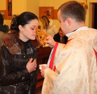 a beautiful young brunette Catholic woman in a Church kissing relics of a saint, photo 2