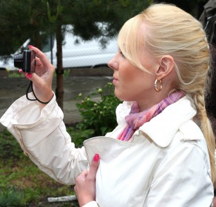 a young blond woman taking a picture near a church in May 2013