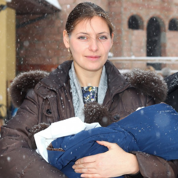 a beautiful Catholic godmother after the baptism of the baby, snowing, photo 11
