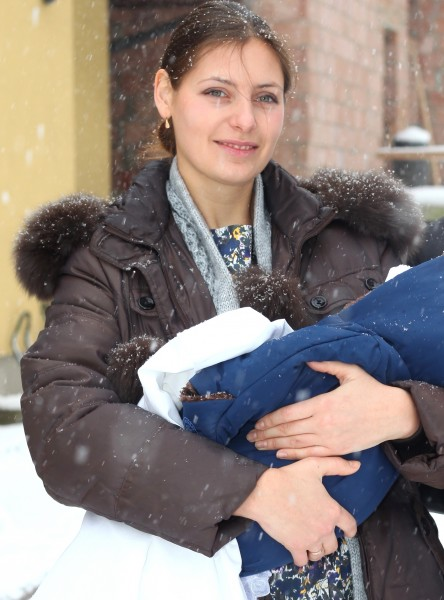 a beautiful Catholic godmother after the baptism of the baby, snowing, photo 3