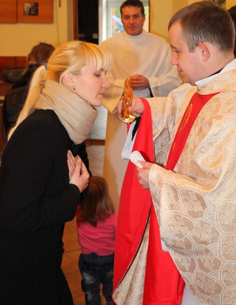 an amazingly tender and charming beautiful young blond Catholic woman in a Church kissing relics of a saint, photo 23