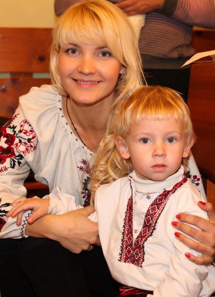 an amazingly tender and charming beautiful young blond Catholic woman with her son in a Church, photo 26