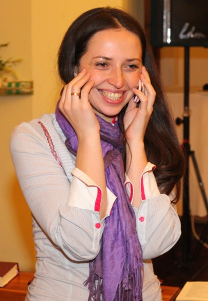 an amazingly attractive smiling charming beautiful young brunette Catholic woman talking over a mobile phone, photo 2