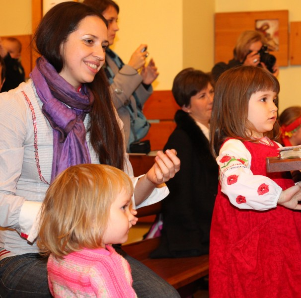 an amazingly attractive smiling charming beautiful young brunette Catholic woman in a Church and two cute child girls, photo 5