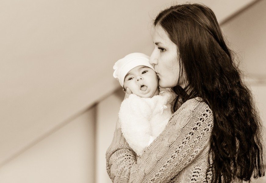 a beautiful young Catholic woman kissing her baby in November 2014, black and white