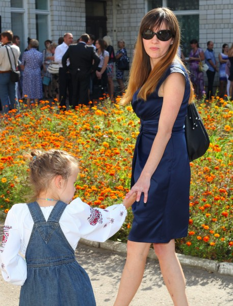 a beautiful young brunette woman in a dress and in sunglasses, with a child girl, photo 3