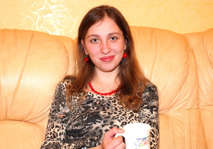 a charming young brunette Catholic woman on a leather sofa, picture 19
