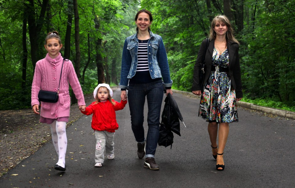 four young Catholic females walking through a park in June 2013