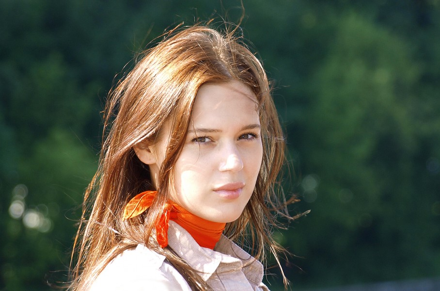 a woman with a light brown blouse and a red scarf
