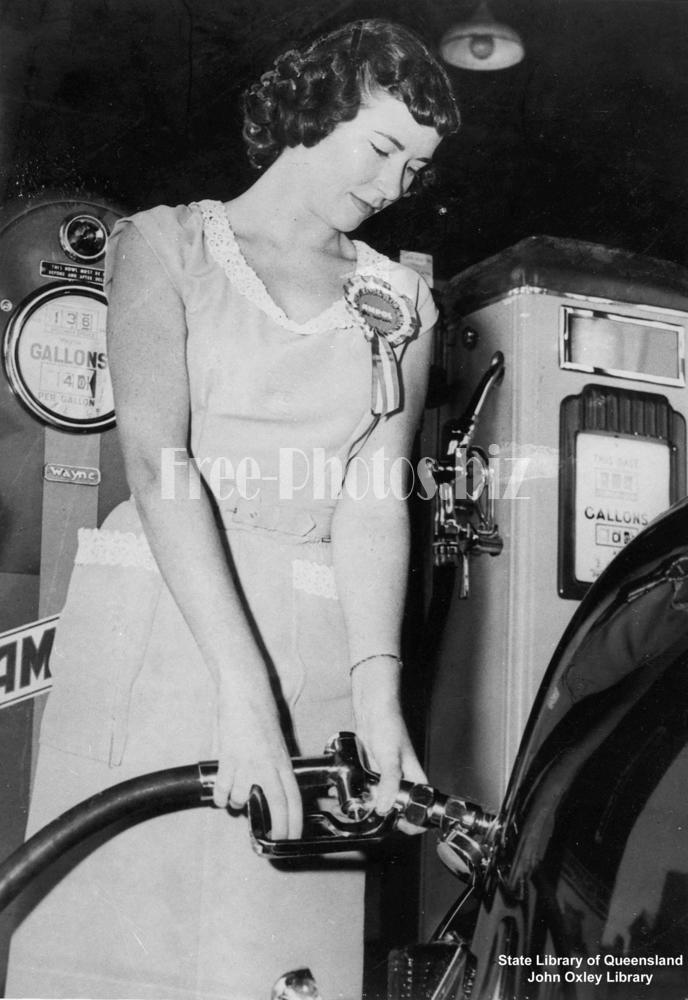 a woman using a petrol pump at a service station, 1952 StateLibQld 1 118936