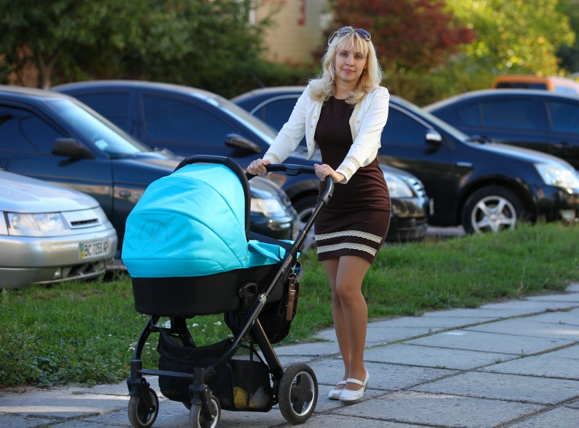 a young Catholic mother with her third kid in a pram in September 2013