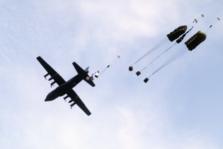 A C-130 Hercules aircraft drops supplies by parachute to troops during Exercise Volant Shield DF-ST-89-06582