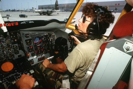 A ground crew member sits in the co-pilot's seat of a KC-135 Stratotanker aircraft as she helps conduct a maintenance check during Operation Desert Shield DF-ST-91-08793