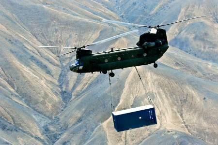 A U.S. Army CH-47 Chinook helicopter carries a sling-loaded shipping container during retrograde operations and base closures in the Wardak province of Afghanistan 131026-A-SM524-737