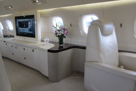 Embraer Lineage 1000 interior with tv and credenza