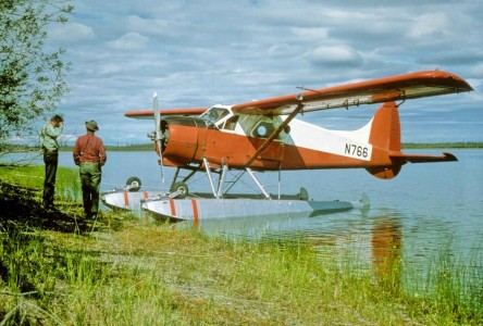 Float aircraft on shore with poeople beside