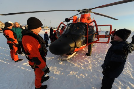U.S. Coast Guard Petty Officer 2nd Class Chad Griffin, an aviation mechanic, speaks to a Nome, Alaska, resident about working aboard a Coast Guard MH-65 Dolphin helicopter in Nome Jan 120118-G-YE680-099