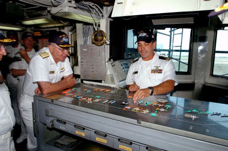 US Navy 040505-N-6213R-028 Adm. Vern Clark, Chief of Naval Operations (CNO), looks on as Lt.j.g. David Martinez demonstrates flight deck operating procedures in Flight Deck Control