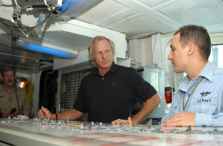 US Navy 041011-N-4565G-002 Aviation Boatswain Mate 3rd Class Greg Black explains the oujia board, in Hangar Deck Control, to professional golfer Greg Norman